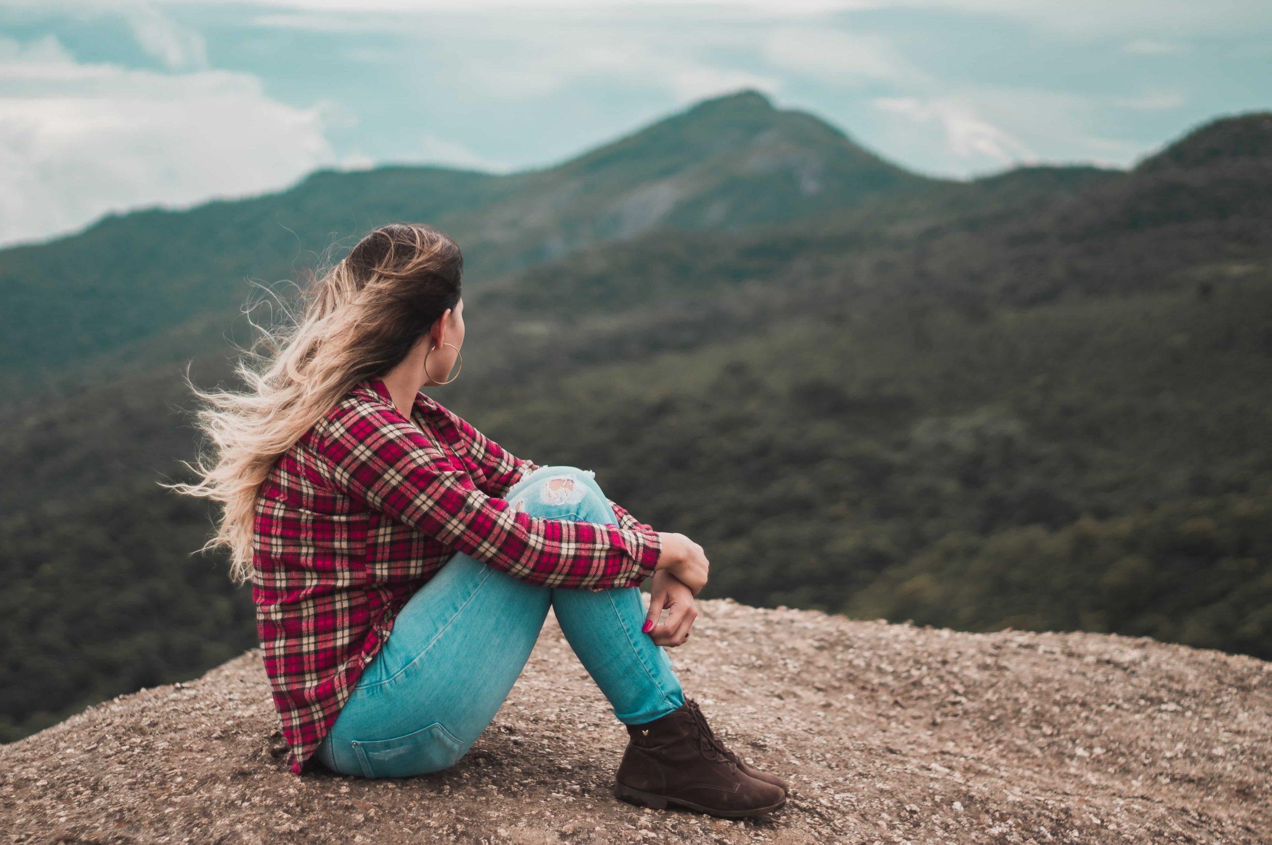 femme pensant devant un paysage de montagnes