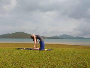 gérer son stress : femme faisant du yoga posture chameau à l'extérieur