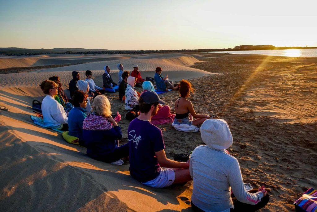 gérer son stress : groupe de personnes méditant sur la plage